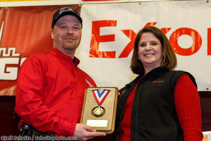 ExxonMobil representative Karen Hagedorn presents Aaron Burmeister with the ExxonMobil Musher's Choice Award at the musher 's finishers banquet in Nome on Sunday March 16 after the 2014 Iditarod Sled Dog Race.<br /> <br /> PHOTO (c) BY JEFF SCHULTZ/IditarodPhotos.com -- REPRODUCTION PROHIBITED WITHOUT PERMISSION