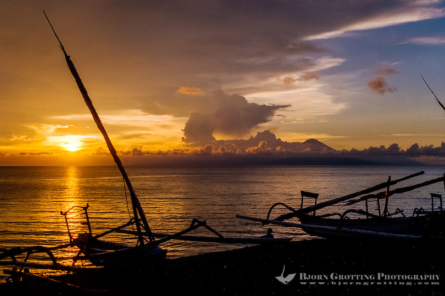 Nusa Tenggara, Lombok, Senggigi. The sun sets in the ocean, in the backgrund you can see Gunung Agung on Bali.