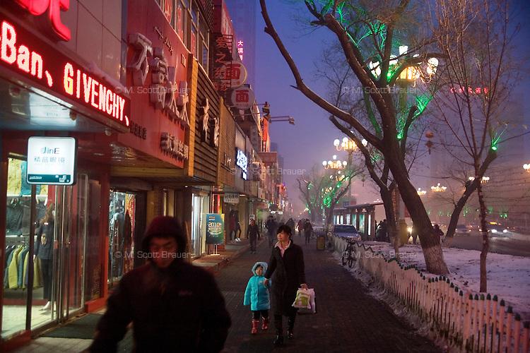 People walk along the streets of a shopping district in Urumqi, Xinjiang, China.