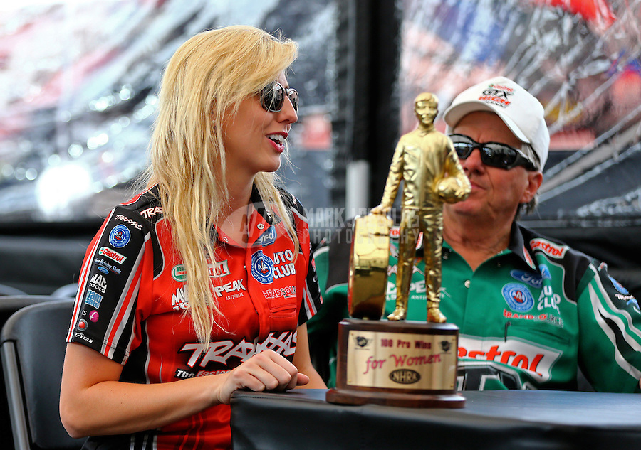 May 30, 2014; Englishtown, NJ, USA; NHRA funny car driver Courtney Force with her 100th female winner trophy alongside father John Force during qualifying for the Summernationals at Raceway Park. Mandatory Credit: Mark J. Rebilas-