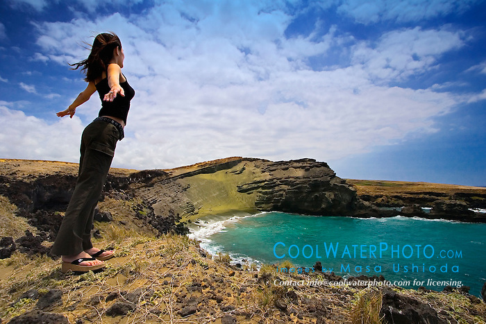 Woman tourist feeling strong wind at Green Sand Beach, Mahana Bay, South Point, Big Island, Hawaii, Pacific Ocean
