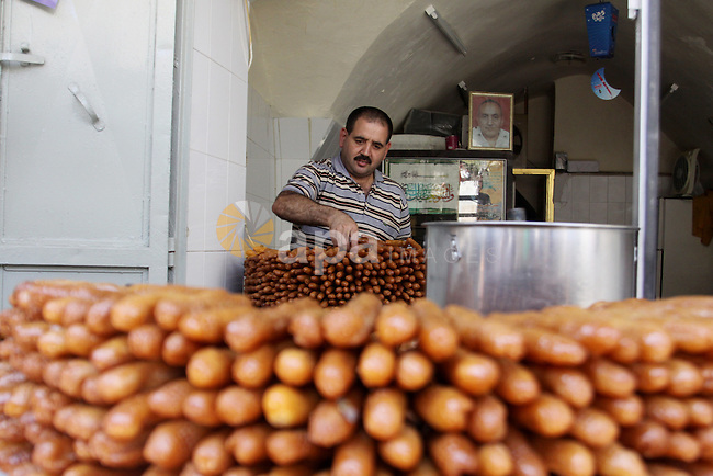 A Palestinian sweet-maker prepares sweets consumed during Ramadan in the West Bank city of Nablus, on July 22, 2012. Muslims around the world abstain from eating, drinking and conducting sexual relations from dawn till dusk during Ramadan, the holiest month in the Islamic calendar. Photo by Nedal Eshtayah