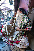 India, Maharashtra, Mumbai, Bombay, red light district. A woman sex-worker stares out from the window of her brothel.