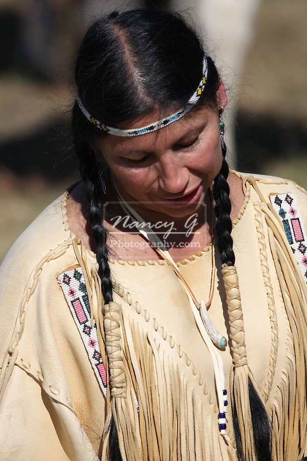 A Native American Indian with fringe leather dress and braids