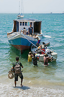 Timorese men load passengers' luggage onto a boat in Dili harbor for a trip across the Wetar Strait to Atauro Island, Timor-Leste (East Timor)