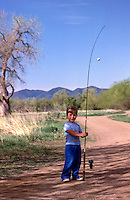 Boy fishing in Colorado pond with mountains in background. Model released.