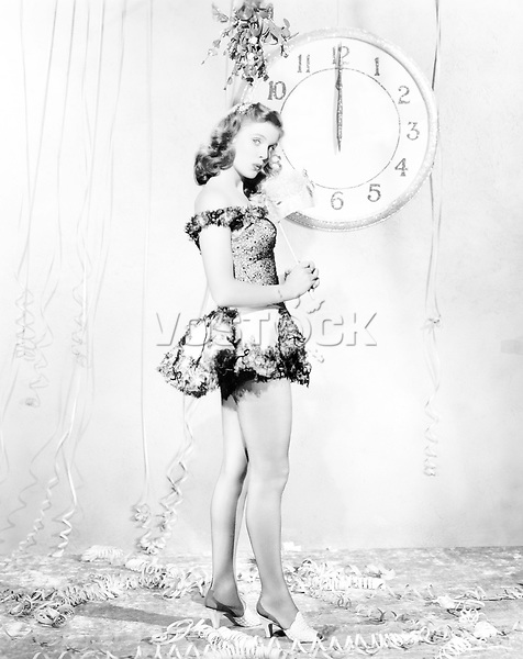 Young woman standing in front of a clock, celebrating New Years Eve