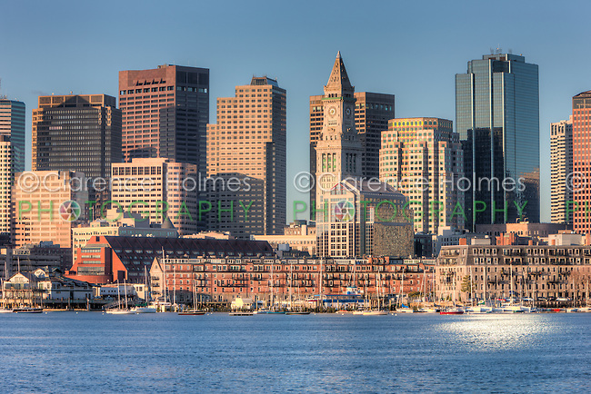 Early morning light reflects off the Custom House Tower, skyscrapers in the Financial District, and low rise wharves on the waterfront which make up part of the eclectic skyline of Boston, Massachusetts.