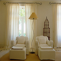 A pair of armchairs in white loose covers with matching footstools in a corner of the main bedroom with a birdcage against the wall behind