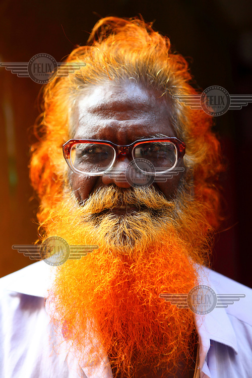 An old man who dyed hair.<br /> <br /> It is very common in Bangladesh to see older people with dyed orange hair, men with orange beards or orange moustaches and women with orange hair. The dye used is from the flowering Henna plant. The practice comes from the widely held belief that the Prophet Muhammad dyed his beard and hair. It is also common among people returning from Hajj. Some Muslims believe that henna is the only dye they are free to use for colouring their hair.