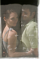 Man and woman behind window screen