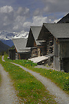 Mountain trail alongside wooden cabins with steep roofs. Hahntennjoch pass, between Imst and Elmen, Tyrol. Austria.