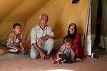 DOMIZ, IRAQ: Yousif Farzan Bozo and his family sit in their tent in the Domiz refugee camp...Over 7,000 Syrian Kurds have fled the violence in Syria and are living in the Domiz refugee camp in the semi-autonomous region of Iraqi Kurdistan...Photo by Ali Arkady/Metrography