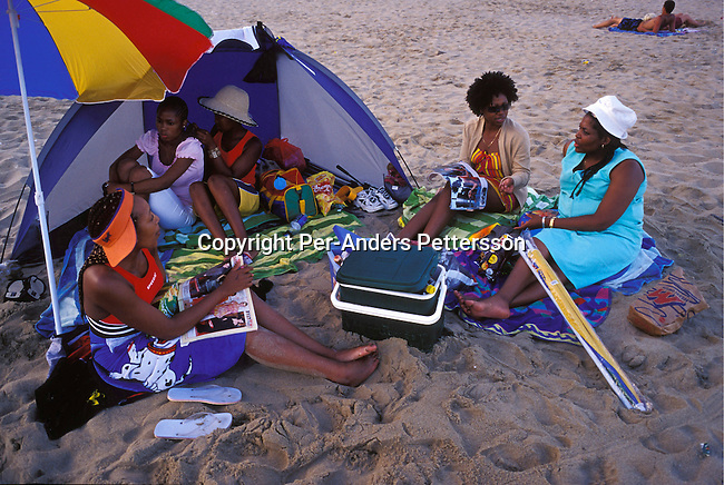 dipplei00069.People Leisure, Margate, South Africa: Unidentified up-market black South Africans, on holiday, enjoys the beach on January 2, 2004 in Margate, a holiday resort town on the Natal South Coast, South Africa. A growing number of people belong to the new black elite in the country. Well educated and connected, they have risen from the poverty in the townships to a very different lifestyle, since the fall of Apartheid and the start of democracy in the country in 1994. Many of these families have money to spend on houses, cars, and holidays. .©Per-Anders Pettersson/iAfrika Photos...