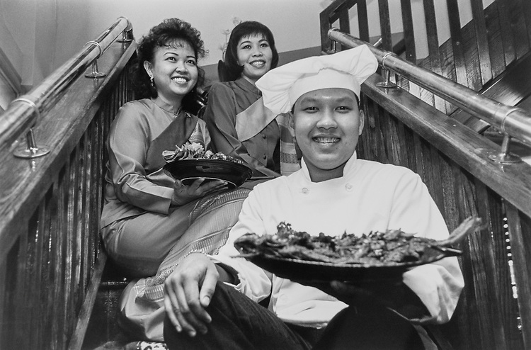 Chef Peter Valikit holds Pla-Lard-Prix, deep fried Flounder with hot chili and basil. Waitress Wuankipa Lim holds Gang sup-pa-rod, shrimp curry with fresh pineapple served in whole pineapple, Vdom Tongrugs on the right. (Photo by Laura Patterson/CQ Roll Call via Getty Images)