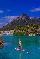 Woman doing standup paddleboard yoga in the lagoon, Four Seasons Resort Bora Bora, French Polynesia.