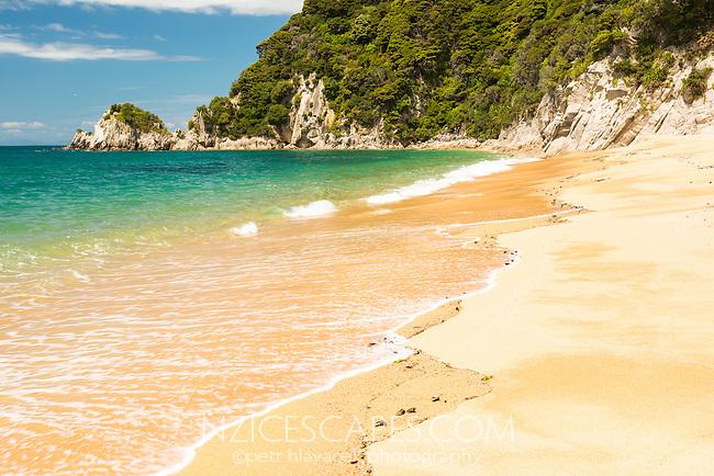 Turquoise waters and golden sand of Anatakapau Bay on Abel Tasman Coast Track, Abel Tasman National Park, Nelson Region, South Island, New Zealand
