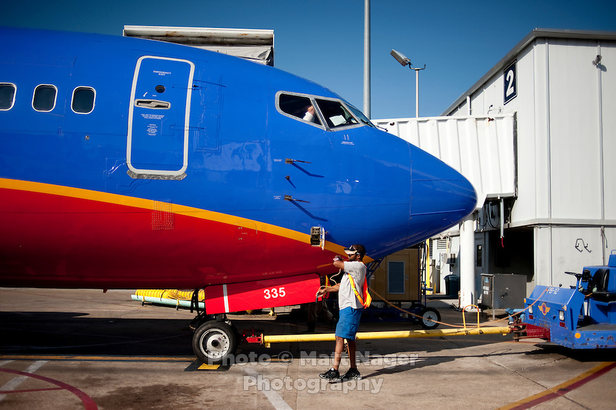 "Southwest Airlines employee Fabian Cordova (cq) prepares a plane for takeoff at Love Field Airport in Dallas, Texas, Wednesday, October 27, 2010. A big selling point for Southwest Airlines has been their ""Bags Fly Free"" campaign...PHOTO/ MATT NAGER"
