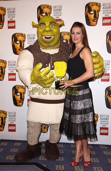 SHREK & KIRSTY GALLACHER.British Academy Children's Film & Television Awards in Association With The Lego Company, Hilton Hotel, London..November 28th, 2004.Baftas, full length, red shoes, black chiffon dress, award, trophy.www.capitalpictures.com.sales@capitalpictures.com.© Capital Pictures.