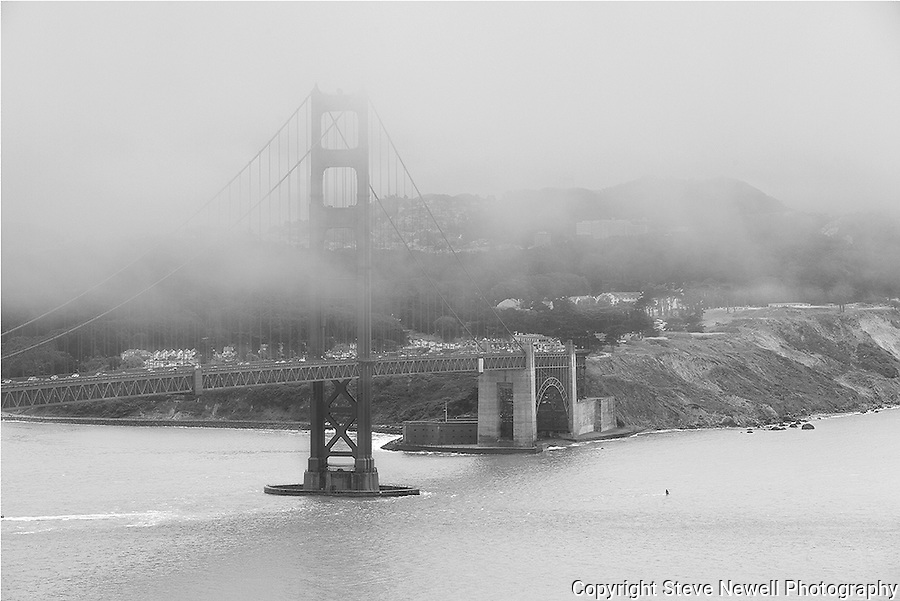 """Park and Ride""  Black and White Golden Gate Bridge and The Presidio Park, San Francisco.  This close up of the bridge with the Presidio behind it was taken from the Marin side of the Golden Gate Bridge.  I was lucky to have the clouds blowing in off the Pacific Ocean and was changing every ten minutes."