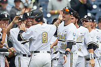Vanderbilt Commodores outfielder Rhett Wiseman (8) is greeted by his teammates after scoring during the NCAA College baseball World Series against the Cal State Fullerton Titans on June 15, 2015 at TD Ameritrade Park in Omaha, Nebraska. Vanderbilt beat Cal State Fullerton 4-3. (Andrew Woolley/Four Seam Images)