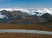 Two bike riders high above the clouds in HALEAKALA NATIONAL PARK on Maui in Hawaii USA