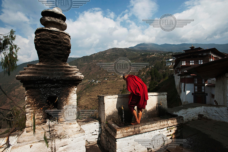 A monk washes his feet while standing in a large outside sink at the Trongsa Dzong Monastery.