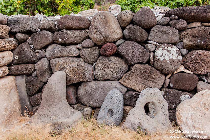Authentic Hawaiian stone anchors along stone wall canoe shelter in Nualolo Kai village, Na Pali coast, Kauai