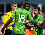 Assistant Referee Jeff Hosking, left, and Gonzalo Pineda, left, and Sounders'  separates Seattle' Djimi Traore (18) and Colorado Rapids Edson Buddle during an MLS match on April 26, 2014 in Seattle, Washington.  The Seattle Sounders beat the Colorado Rapids 4-1.  Jim Bryant Photo. ©2014. All Rights Reserved.