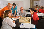Two older men and one younger man and two young women at desks in college classroom talk about the scaled model for architectural landscape class