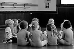 Young ballet dancers at a ballet class sitting in a circle listening to the instructions from the ballet teacher with one boy in class