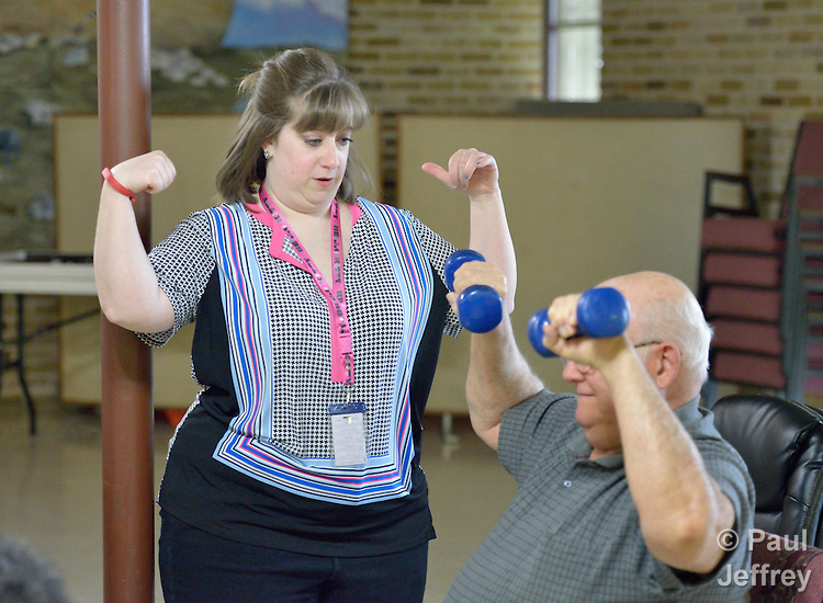 Donnelle Storrs, a faith community nurse at Chapel Hill United Methodist Church in San Antonio, Texas, helps encourage a man as she leads an exercise group at the church.