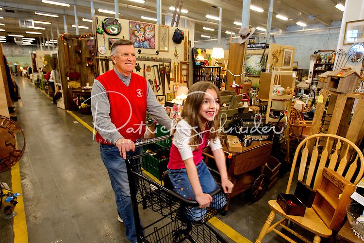 Patrick Carney from Charlotte, North Carolina, pushes his grand daughter, Molly Carney , 6, thru the Depot at Gibson Mill. The Depot at Gibson Mill, an antique and designer mall that was once a mill, located in Concord, N.C. With 85,000 square feet and 460 booths, the antique mall is one of the largest antique and designer mall in the South. Once a part of the old Cannon Mills, the charm of the 20 foot ceilings, wide wooden floors and exposed brick remains. Photo is part of a photographic series of images featuring Concord, NC, by Charlotte-based photographer Patrick Schneider..