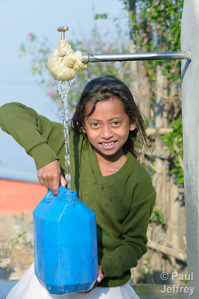 A girl fills a container with water at a community spigot in Makaising, a village in the Gorkha District of Nepal that was hard hit by a devastating 2015 earthquake.