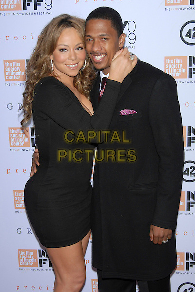 "MARIAH CAREY & NICK CANNON .At the 47th Annual New York Film Festival Centerpiece Screening of ""Precious"" held at Alice Tully Hall, Lincoln Center, New York, NY, USA, October 3rd, 2009. .half length black dress mini hand touching face coat maroon burgundy tie profile husband wife couple married sleeves  hugging .CAP/LNC/TOM.©LNC/Capital Pictures"