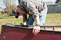 A canoeist drills holes for adding float bags to a canoe prior to a whitewater canoe trip.