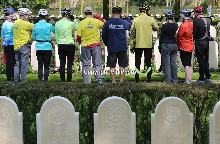 Foto: VidiPhoto<br /> <br /> RHENEN - Amerikaanse senioren brengen maandag op op Militair Ereveld Grebbeberg een eregroet bij de graven van Nederlandse soldaten. De groep, afkomstig uit de VS en Canada, maakt een twaalfdaagse fietstocht door Nederland, waarbij speciale aandacht is voor de militaire historie van ons land. De fiets-vaarvakantie is begonnen in Amsterdam. De hoofdstad is tevens het eindpunt van de Amerikanen. Op het ereveld in rhenen liggen meer dan 850 Nederlandse militairen begraven die gesneuveld zijn tijdens (voornamelijk) de meidagen van 1940 in de strijd tegen de Duitsers. In mei is het altijd extra druk op de begraafplaats met schoolexcursies en bezoekers vanuit het hele land en zelfs van buiten Europa. De nationale herdenking op de Grebbeberg wordt komende woensdag bijgewoond door prinses Margriet en mr. Pieter van Vollenhoven.