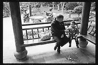 An elderly man eats snacks with his granddaughter along the ancient Beijing-Hangzhou Grand Canal in Hangzhou, Zhejiang province, China, March 2013.
