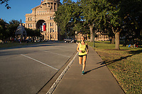 Young fit woman running at the Austin, Texas State Capitol, government seat of Texas on a beautiful sunny day in downtown Austin, Texas.