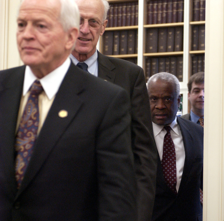 Supreme Court Justice Clarence Thomas, right, makes his way into a hearing of the House Appropriations Subcommittee, alonside Rep. Joe Knollenberg, R-Mich., and John Olver, D-Mass.  The hearing was to discuss the FY 2006 budget for the Supreme Court.  Justice Anthony Kennedy also apeared.