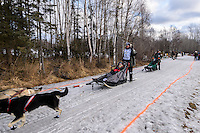 Lachlan Clarke and team run past spectators on the bike/ski trail with an Iditarider in the basket during the Anchorage, Alaska ceremonial start of the 2015 Iditarod race. Photo by Ed Bennett/IditarodPhotos.com