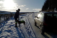 Car passing a walker and her dog on an icy snow covered road. The Lake District.