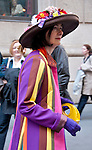 A woman in the Easter Parade in New York City wearing large hat with flowers on top of it, a coat made of colorful stripes, and carrying a bright yellow handbag