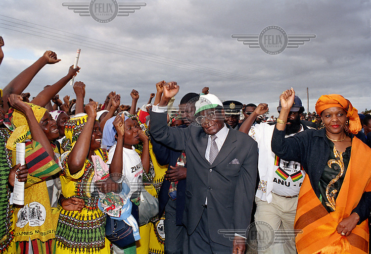 President Mugabe raises a fist with a crowd of supporters during rural campaigning before the 2000 elections. /Felix Features