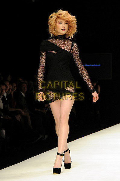 NICOLA ROBERTS.The Fashion For Relief Haiti 2010 show for London Fashion Week Autumn/Winter 2010 at Somerset House, London, England..February 18th, 2010.LFW catwalk runway full length black dress sleeves lace mini .CAP/CAS.©Bob Cass/Capital Pictures.