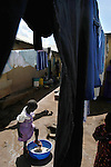 Ayoo Particia, 6,  washes her shoes after washing herself  in  among the drying laundry in the Soweto, section of Kampala Uganda  November 12, 2003. (Rick D'Elia)<br />