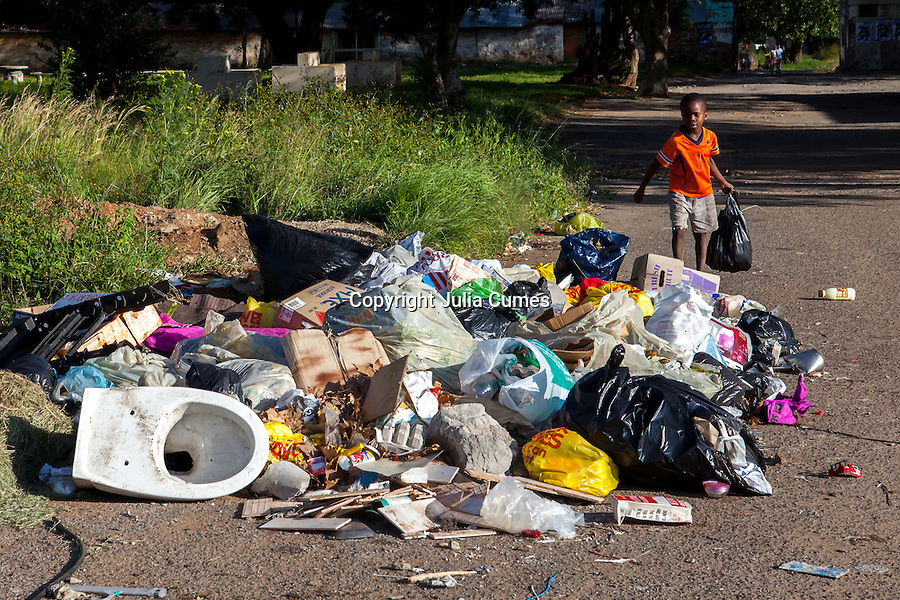 A young boy brings a bag of trash to a makeshift dumping site outside Skomplaas hostel on the outskirts of Johannesburg, South Africa.
