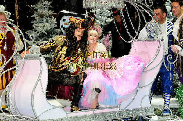 DAVID HASSELHOFF & BARBARA WINDSOR .First Family Entertainment theatre company's annual group Pantomime photocall at Piccadilly Theatre, London, England..November 26th, 2010.stage costume panto pantomime full length captain hook fairy godmother carriage sitting pink dress gold wig jacket sleigh .CAP/CAS.©Bob Cass/Capital Pictures.