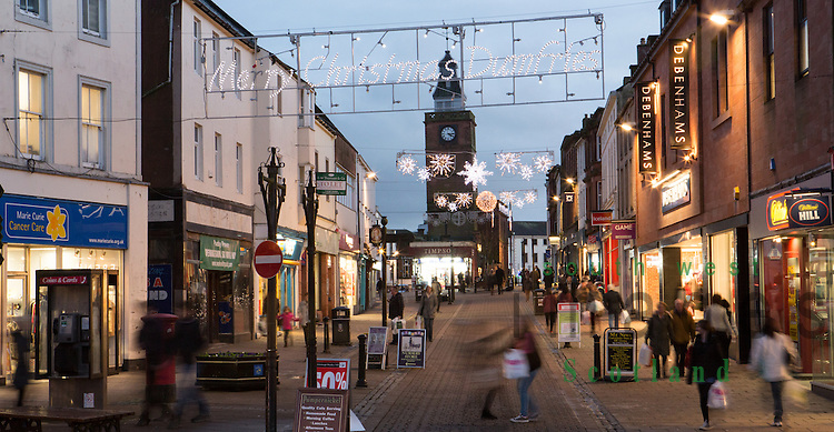 Shoppers shopping under Christmas lights at dusk looking along High Street to Midsteeple in the town centre of Dumfries Scotland