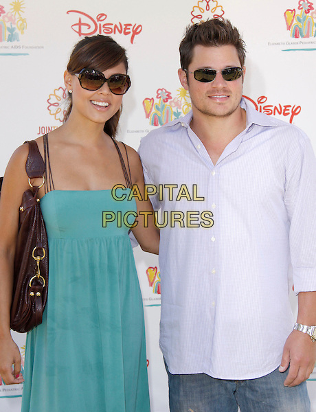 """VANESSA MINNILLO & NICK LACHEY.The 20th annual """"A Time for Heroes"""" Celebrity Carnival benefiting Elizabeth Glaser Pediatric AIDS Foundation held at Wadsworth Theater on the Veteran Administration Lawn in West Los Angeles, California, USA. .June 7th, 2009.half length blue dress teal brown bag purse sunglasses shades purple shirt .CAP/DVS                                                  .©Debbie VanStory/Capital Pictures."""